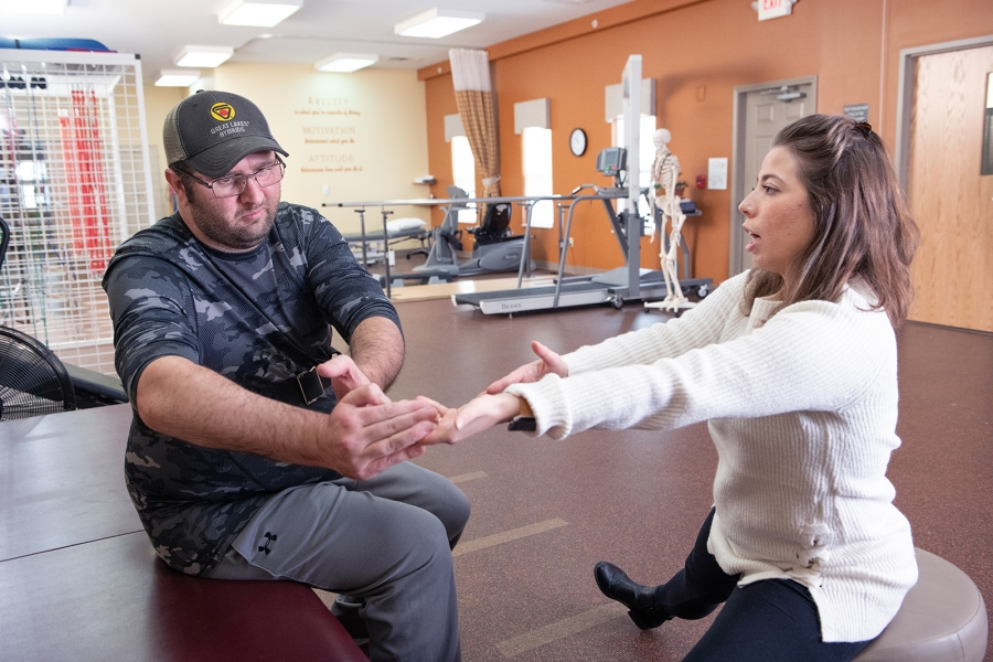 Physical therapists does PWR!Moves with client in the therapy gym.