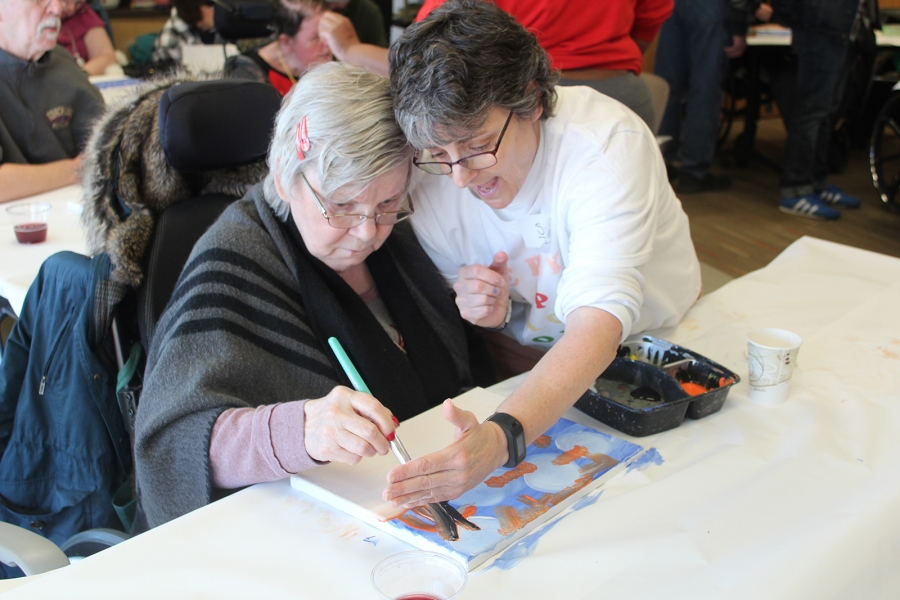A volunteer helps a client hold a pencil to draw a picture.