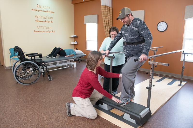 Physical therapist works with client in the gym on the paralell bars.