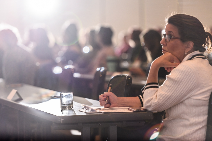 A 2018 Symposium attendee listens eagerly and takes notes during a presentation