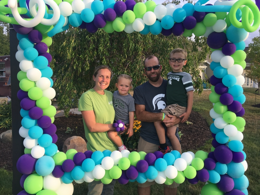 A family enjoys the fun of the concert and snaps a picture in the balloon frame