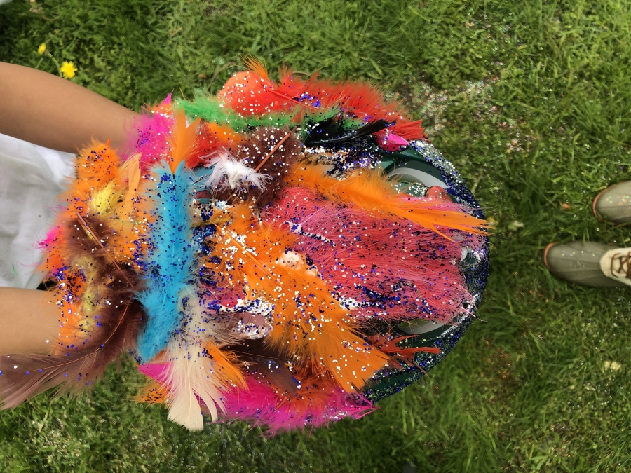 A child holds their newly decorated helmet that's covered in multi-colored feathers and glitter