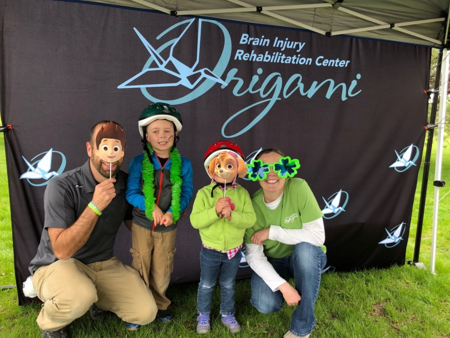 A family of four has some fun in the Origami photo booth at the Lids for Kids 2019 event