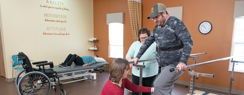 Physical therapist works with client in the therapy gym.