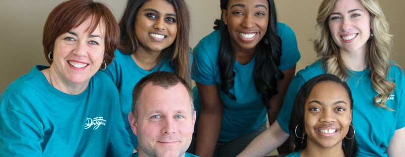 Origami team members in their teal Origami shirts gather for a group photo